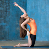 Beautiful woman doing one-legged Camel Pose Stock Photography