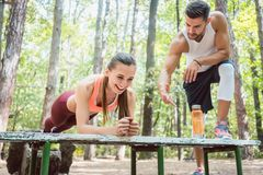 Beautiful woman doing a plank with man watching Stock Photos