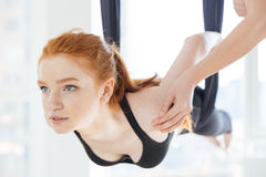 Beautiful woman doing pose of aerial yoga with personal trainer stock images