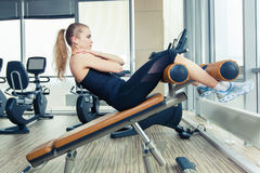 Beautiful woman doing press fitness exercise at sport gym. Stock Photos