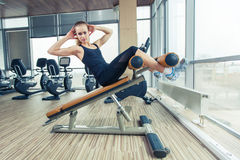 Beautiful woman doing press fitness exercise at sport gym. Stock Photo
