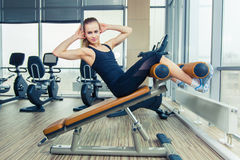 Beautiful woman doing press fitness exercise at sport gym. Doing sit ups in gym Stock Images