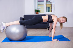 Beautiful woman doing push up exercise with fit ball Stock Images