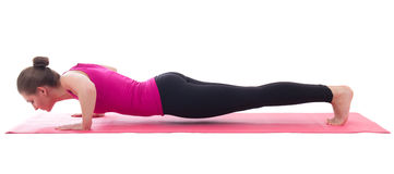 Beautiful woman doing push up exercise on yoga mat isolated on w Royalty Free Stock Photos