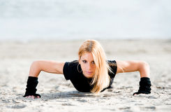 Beautiful woman doing push ups on the beach Stock Image