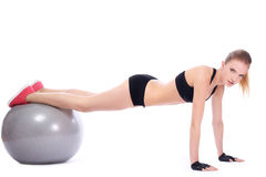 Beautiful woman doing push ups on fitness ball. Over white background stock photos