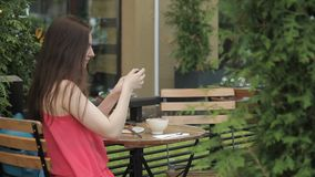 Beautiful woman doing selfie, sitting in summer cafe outdoors. stock video footage