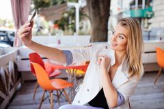 Beautiful young woman is doing selfie using a smart phone and smiling while resting in cafe Stock Photo