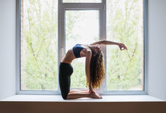 Beautiful woman doing split yoga asana half camel pose on window Royalty Free Stock Photo