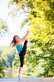 Beautiful woman doing standing splits in park Royalty Free Stock Photos