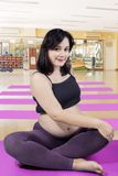 Beautiful woman doing a workout in pregnancy. Beautiful woman looking at the camera while doing a workout in pregnancy. Shot in the gym center stock photo