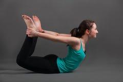Beautiful woman doing yoga dhanurasana. Beautiful woman doing yoga on a gray background Stock Photos