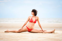Beautiful woman doing yoga exercise on the beach Stock Photo