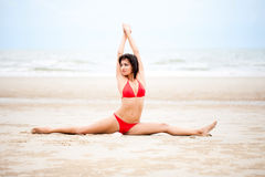 Beautiful woman doing yoga exercise on the beach Stock Images