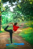beautiful woman doing yoga On green grass Royalty Free Stock Image