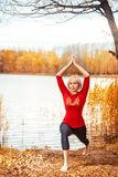 Beautiful woman doing yoga outdoors in autumn stock photography