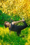 Beautiful woman doing yoga outdoors On green grass Stock Photography