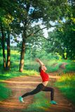 Beautiful woman doing yoga outdoors On green grass Royalty Free Stock Photography