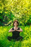 Beautiful woman doing yoga outdoors On green grass Royalty Free Stock Photo
