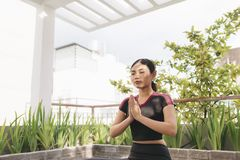 Beautiful woman doing yoga outdoors on a rooftop terrace stock photography