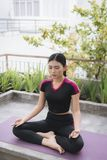 Beautiful woman doing yoga outdoors on a rooftop terrace stock photos