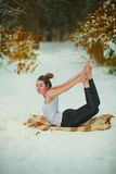 Beautiful woman doing yoga outdoors in snow Royalty Free Stock Photography