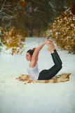 Beautiful woman doing yoga outdoors in snow Royalty Free Stock Images