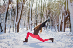 Beautiful woman doing yoga outdoors in the snow royalty free stock photo