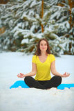 Beautiful woman doing yoga outdoors in the snow Royalty Free Stock Image