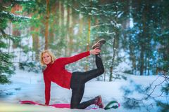 Beautiful woman doing yoga outdoors in the snow royalty free stock images