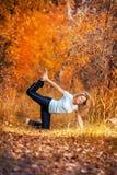 Beautiful woman doing yoga outdoors On yellow leaves Stock Image