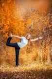 Beautiful woman doing yoga outdoors On yellow leaves Stock Photo