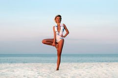 Beautiful woman doing yoga tree pose on the beach stock images