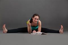 Beautiful woman doing yoga  upavishta konasana. Beautiful woman doing yoga   upavishta konasana on a gray background Royalty Free Stock Photography