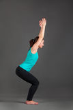 Beautiful woman doing yoga utkatasana. On a gray background Royalty Free Stock Photos