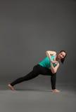 Beautiful woman doing yoga virabhadrasana. Beautiful woman doing yoga on a gray parivritta parshvakonasana Stock Photo