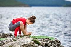 Beautiful woman doing yoga workout outdoor on the rock near the river. Sportive woman in the colorful sportwear and barefoot. Beautiful landscape with river Royalty Free Stock Image