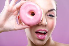 Beautiful woman with donuts, one eye than have a pink donut Royalty Free Stock Photo