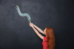 Beautiful woman drawing colorful wave on chalkboard background using pencils Royalty Free Stock Photography