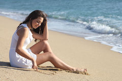 Beautiful woman drawing a heart in the sand Stock Image