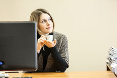 Beautiful woman dreaming with coffee cup at working place Royalty Free Stock Photo