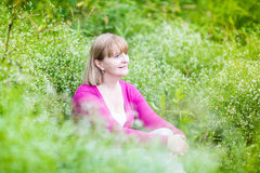Beautiful woman dreaming in garden among flowers Stock Image