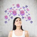 A beautiful woman is dreaming about the gift. Purple gift and heart icons are drawn on the concrete wall. Royalty Free Stock Images