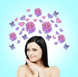 A beautiful woman is dreaming about the gift. Purple gift and heart icons are drawn on the light blue background. A brunette beautiful woman is dreaming about Stock Photography