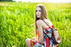 Beautiful woman in dress and bag sitting on the glade Royalty Free Stock Photography