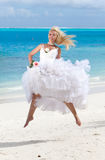 Beautiful woman in a dress of the bride jumps Stock Photos