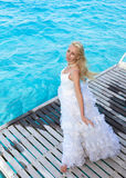 Beautiful woman in a dress of the bride. The young beautiful woman in a dress of the bride  at edge of the sea Royalty Free Stock Photos