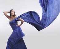 Beautiful woman in dress colour electric blue #3. Studio photo beautiful young mysterious girl in a long silk dress color electric blue, standing in an unusual Stock Images