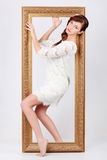 Beautiful woman in dress comes out of frame Stock Photos