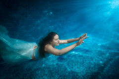 Beautiful woman in dress comes up from pool at beam of light Stock Photos